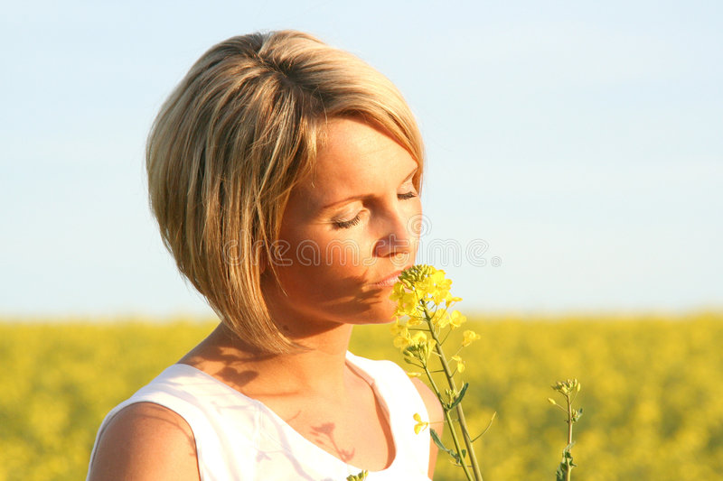 Beautiful Day - Summer time. A beautiful young woman and yellow flowers stock image
