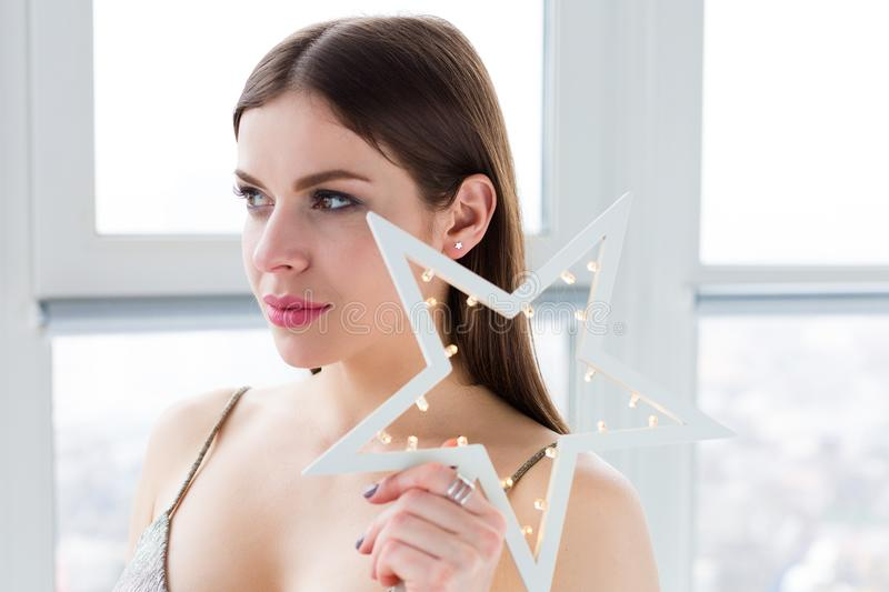Beautiful daydreaming woman. Beautiful young woman dayidreaming by the window stock photography