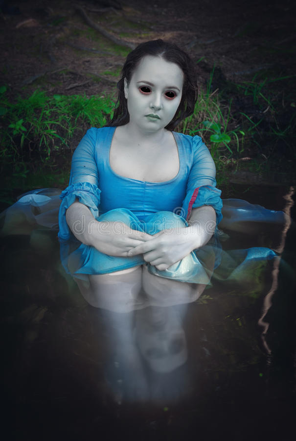 Beautiful dead ghost woman. Sitting in the water stock images