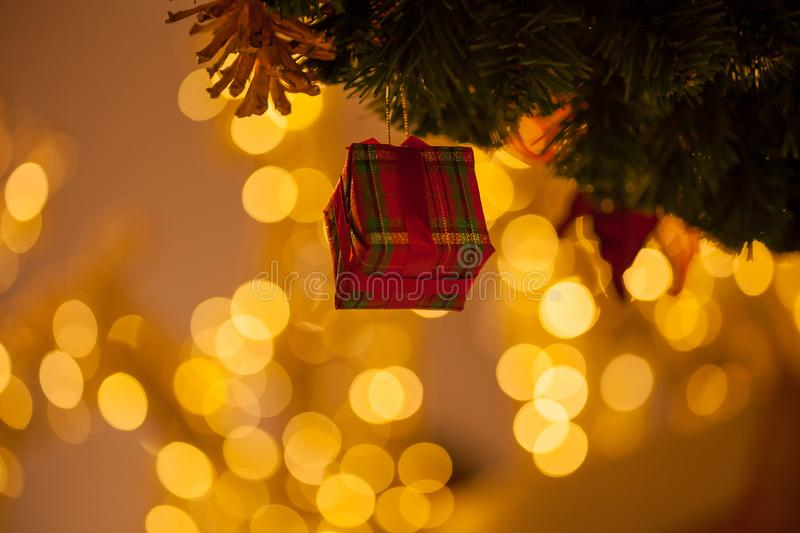 Beautiful decorated Christmas tree background with red gift box and xmas ornaments in close-up shot. royalty free stock photos