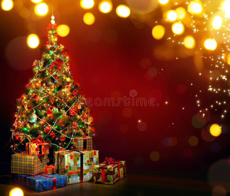 Beautiful decorated Christmas tree with present boxes and magic. Holidays light on red backgroundon stock photography