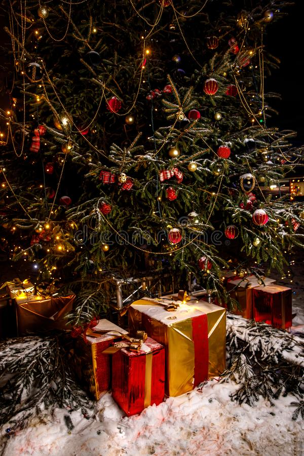 Beautiful decorated christmas tree with present boxes in a winter concept. With snow royalty free stock photo