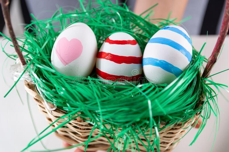 Easter colorful eggs in a retro wooden basket with green grass stock photo