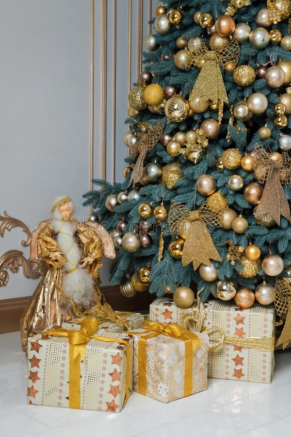 Beautiful decorated golden Christmas tree with present boxes in luxury classic interior. Beautiful decorated golden Christmas tree with present boxes in luxury royalty free stock photos