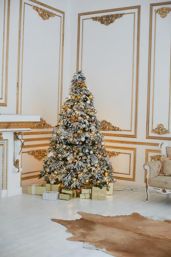 Beautiful decorated golden Christmas tree with present boxes under it in vintage luxurious interior decorated for New. Year. Concept of Christmas eve. Concept stock images