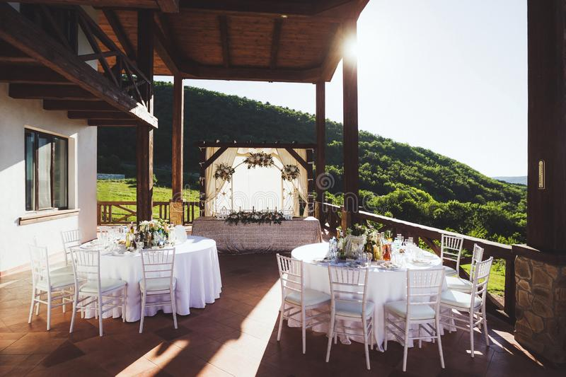 Beautiful decorated wedding ceremony outdoor with mountain view. A lot of white chairs and carved forged arch with flowers stock images