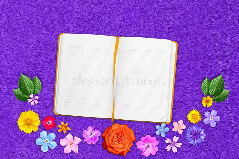 Beautiful decoration flowers frame with notebook in center on purple gentle leather background. Floral composition of spring or su stock image