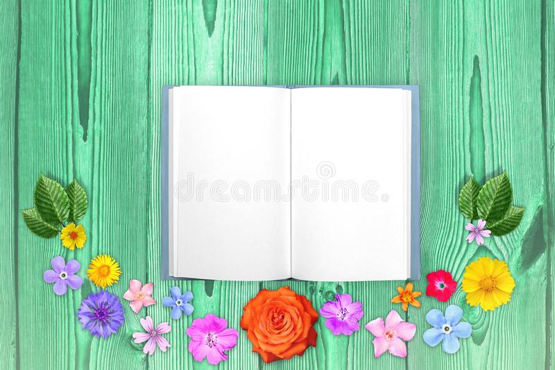 Beautiful decoration flowers frame with notepad in center on purple wooden planks background. Floral composition of spring or summ stock photos