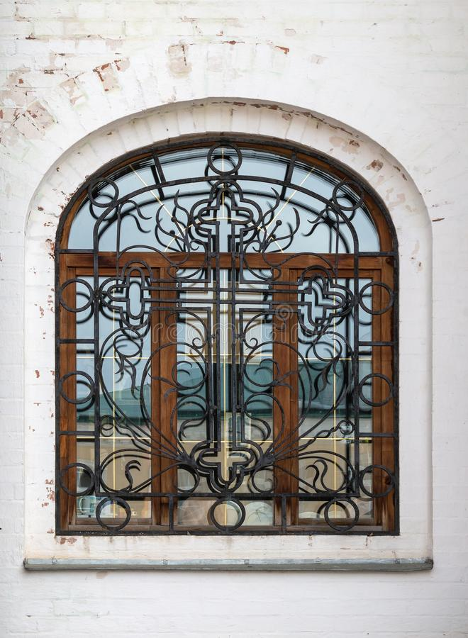 Beautiful decorative stained glass window with openwork wrought-iron lattice in the stone wall. royalty free stock photos