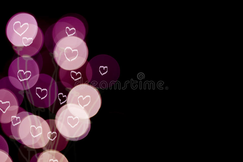 Beautiful defocused LED lights filtered bokeh abstract with illusion hearts on purple-black tone background. royalty free stock photo