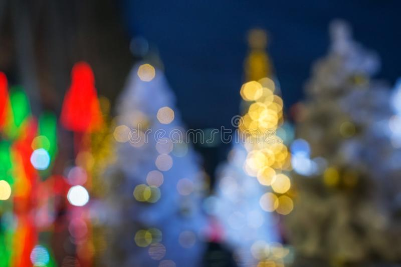 Beautiful defocused white christmas trees and happy new year celebration event light in yellow, green, red and gold color bokeh royalty free stock photos