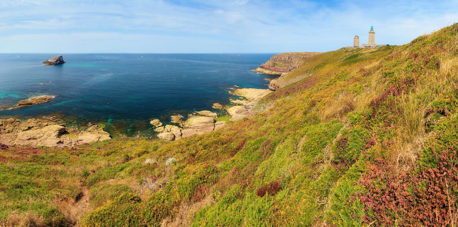 Coastline panorama at Cap Frehel. Beautiful 180 degree panoramic view of the cliffs at Cap Fréhel in Brittany, France, with its lighthouses and moorland with royalty free stock photo