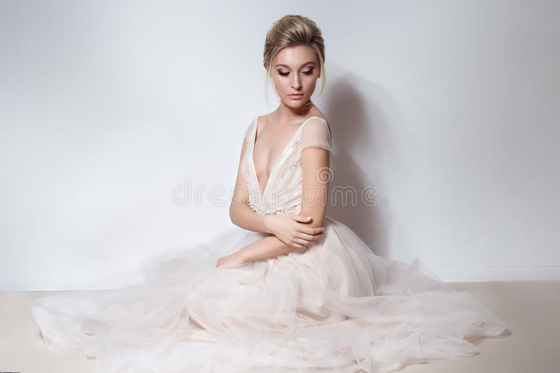 Beautiful delicate bride girl in soft pink skazachno wedding dress with a cut on the chest and back with makeup and evening h. Airstyle in the studio on a white stock photography