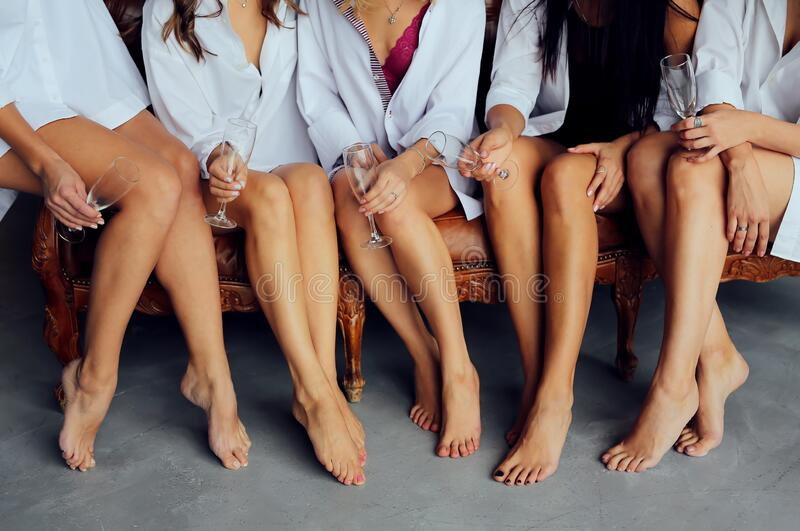 A group of five girls. Tanned, female legs, ankles. Beautiful delicate female legs. A diverse group of girls enjoy a fun party with glasses of wine. The slender royalty free stock images