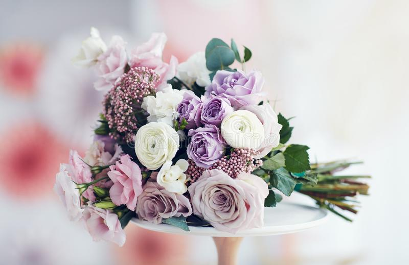Beautiful delicate flower bouquet with roses, ranunculuses, eustomas and carnations. Pastel delicate flower bouquet with roses, ranunculuses, eustomas and royalty free stock image