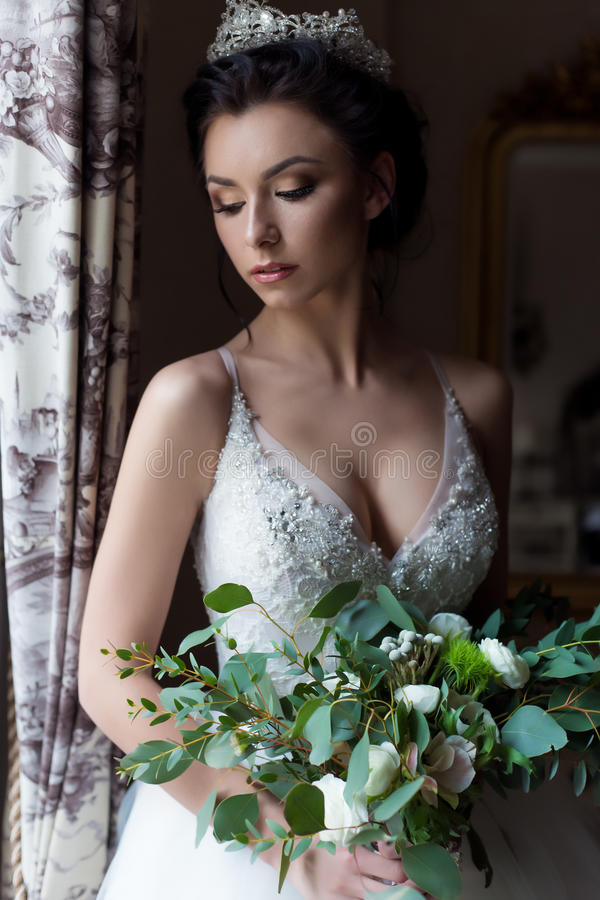 Beautiful delicate bride happy woman with a crown on her head by the window with a large wedding bouquet in a luxurious white. Dress royalty free stock images
