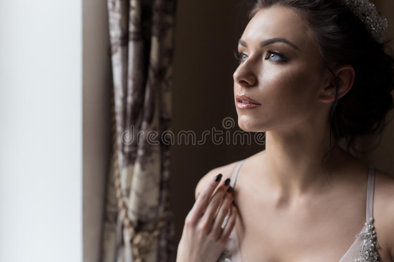 Beautiful delicate bride happy woman with a crown on her head by the window with a large wedding bouquet in a luxurious white. Dress stock image