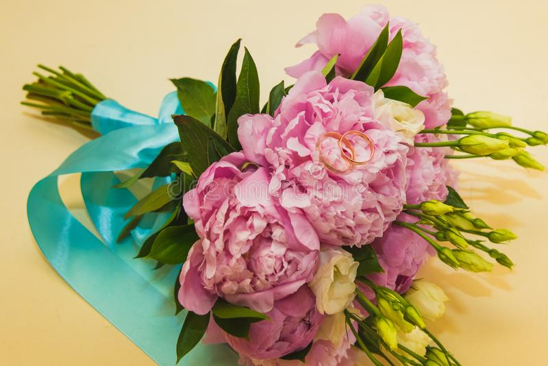 Beautiful delicate wedding bouquet of pink peonies and wedding rings of the bride and groom stock images