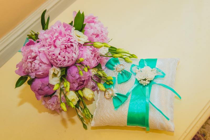 Beautiful delicate wedding bouquet of pink peonies and wedding rings of the bride and groom royalty free stock photography