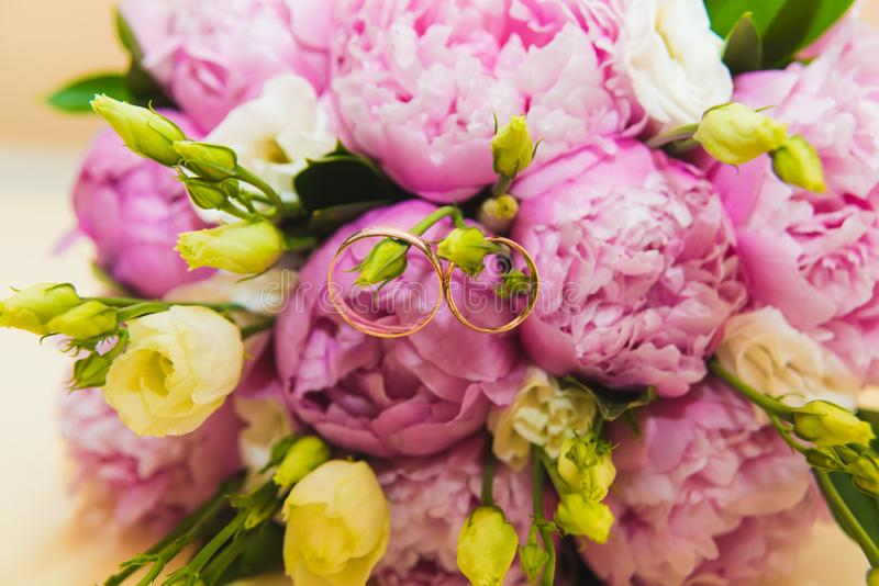 Beautiful delicate wedding bouquet of pink peonies and wedding rings of the bride and groom royalty free stock image