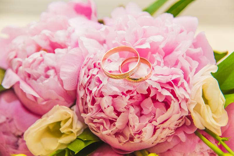 Beautiful delicate wedding bouquet of pink peonies and wedding rings of the bride and groom royalty free stock photo