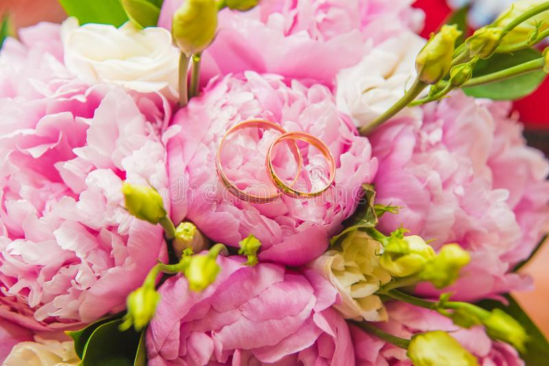 Beautiful delicate wedding bouquet of pink peonies and wedding rings of the bride and groom stock photo