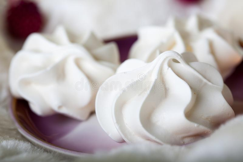 Beautiful delicious white meringues on a purple plate royalty free stock images