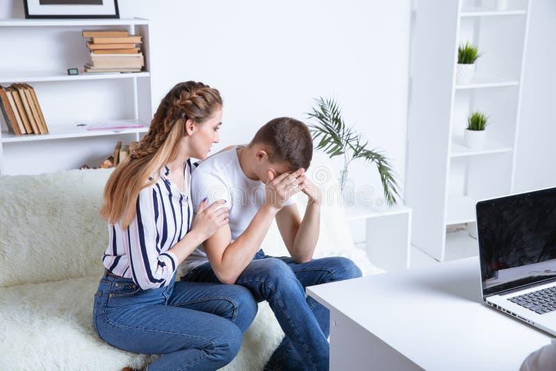 A Beautiful dello psicologo giovane la coppia sta sedendosi sullo strato e sta abbracciando mentre medico sta facendo una nota immagine stock