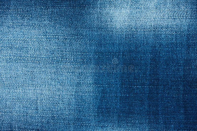 Beautiful denim texture with the effect of aging and scuffs. Fashionable jeans background stock images