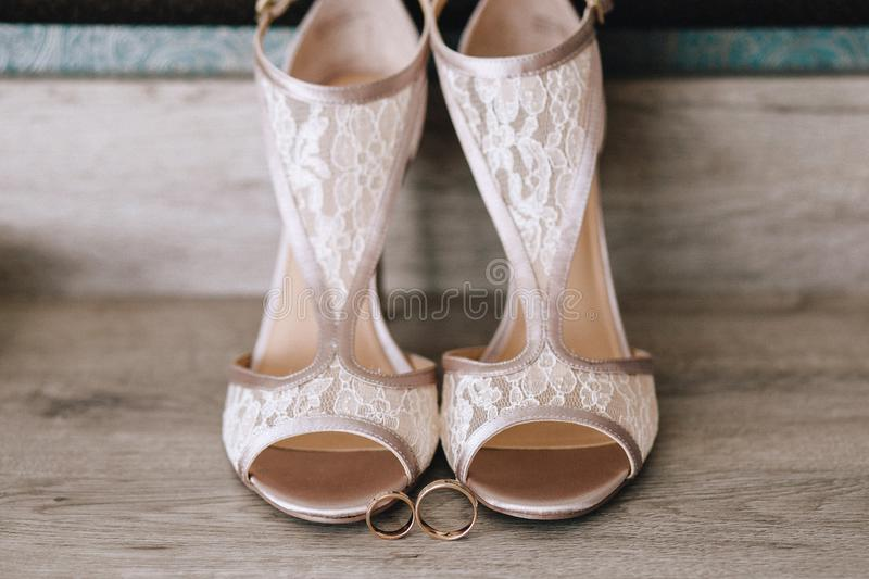 Beautiful designer beige wedding shoes with lace, near gold wedding rings on a parquet stock images