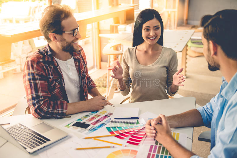 Beautiful designers working. Group of beautiful designers in casual clothes is discussing affairs, choosing colors and smiling while working in studio royalty free stock image