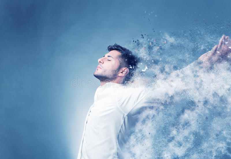 Beautiful destruction. Young man in free spirit with outstretched arms, light blue background with copy space, decomposing into small sand particles royalty free stock photos