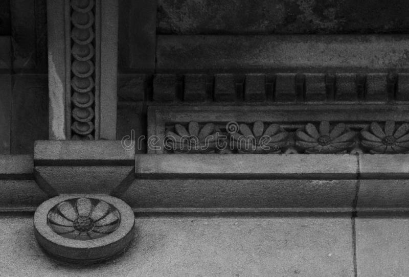 Beautiful detail with round flowers. Shot in black and white detail on the facade of this historic building representing some character, animal or flower. Set in royalty free stock photos