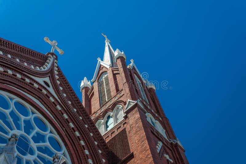 Beautiful details of steeples and rose window, Gothic Revival church, red brick white crosses, blue sky stock image