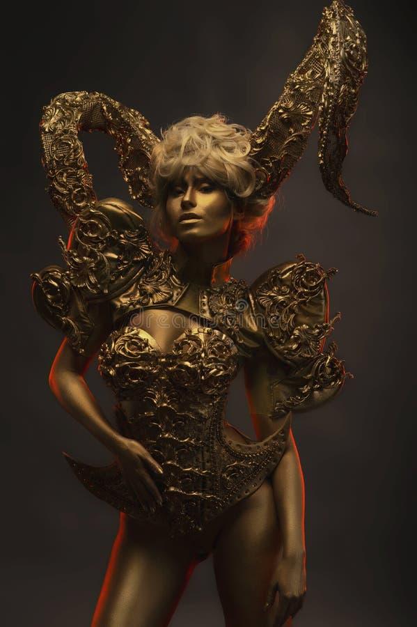 Beautiful devil women with golden ornamental horns. Beautiful devil woman with golden ornamental horns on dark background stock photos