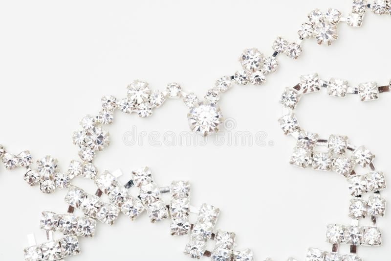 A beautiful diamond halo and white gold pendant dangles from a chain. Fine Jewelry necklace isolated on a white royalty free stock photos