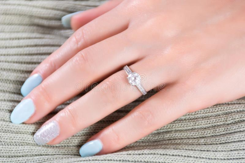 Diamonds wedding engagement rings on female finger with blue nails manicure stock photography