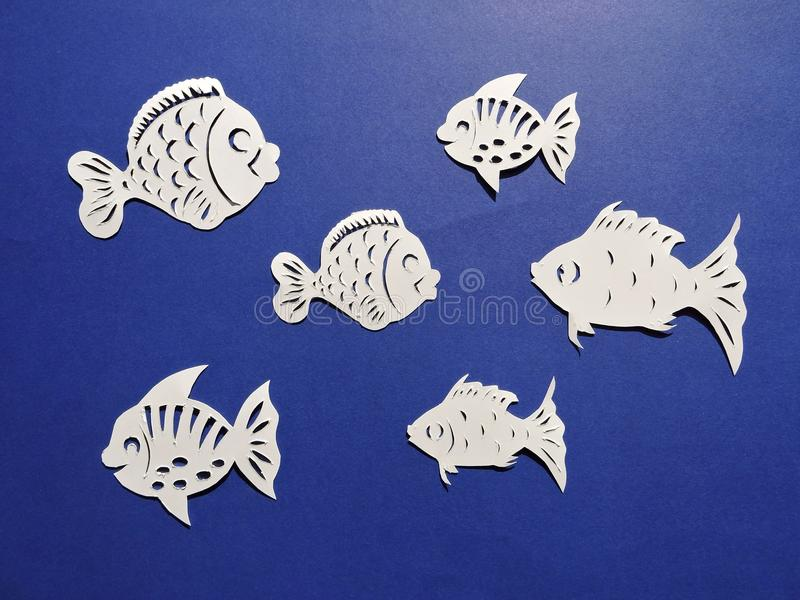 Different shape fish cut from white paper royalty free stock photos