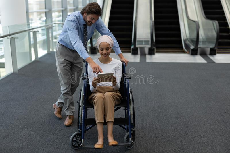 Disabled young mixed-race female executive with Caucasian businessman discussing over digital tablet royalty free stock photography