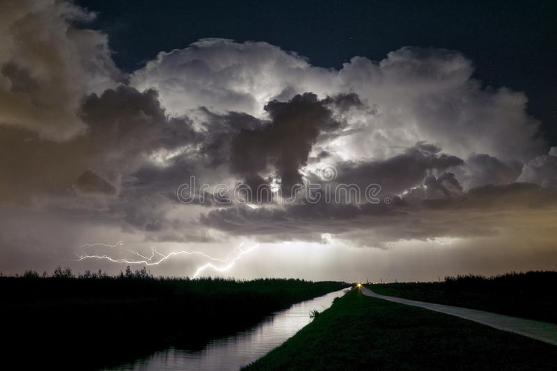 Lightning strike with dramatic thunderclouds as seen from a park in The Netherlands stock photos