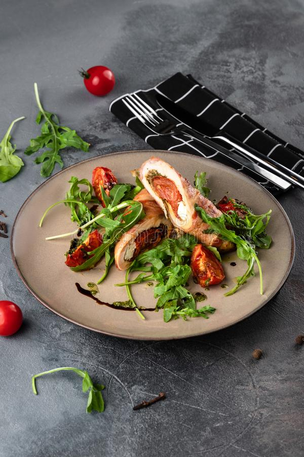 Beautiful dish at grey cement background in rustic style, meatloaf with baked tomatoes and green arugula on beige plate at stock images