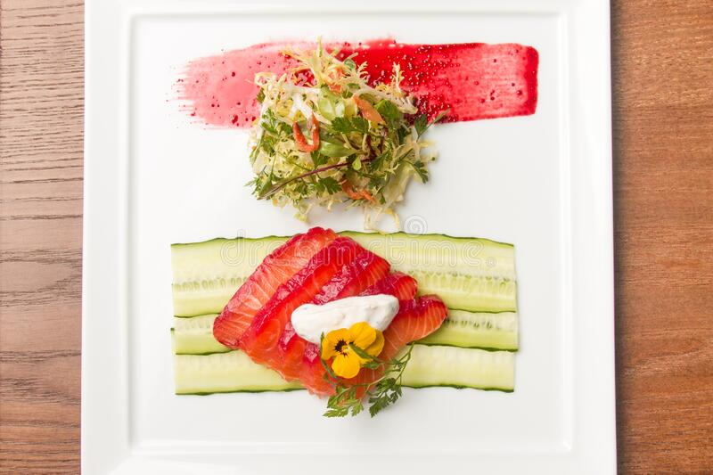 Beautiful dish with red fish vegetables and salad on a white square plate. Food, seafood, delicious, beautiful, restaurant, serving, dish, diet, healthy eating royalty free stock images