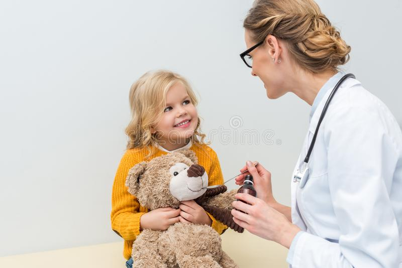 Beautiful doctor giving syrup to teddy bear of. Little girl royalty free stock photography