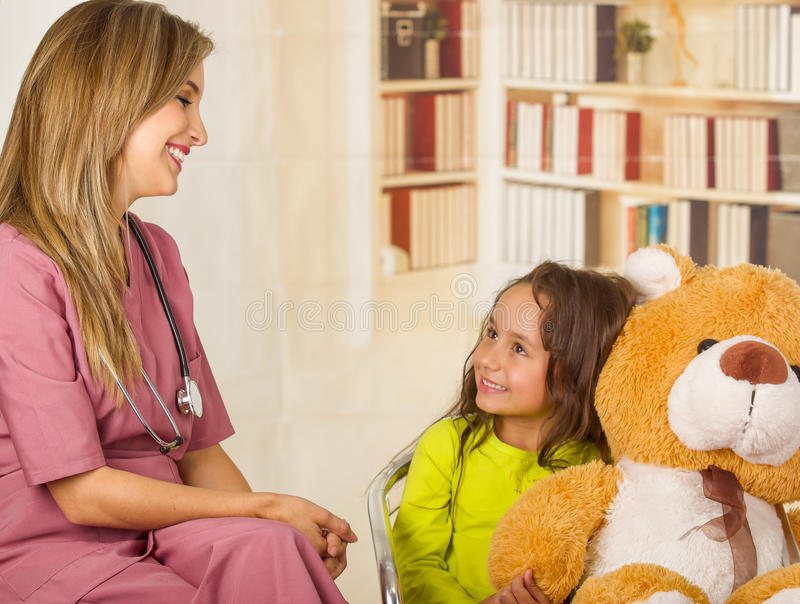 Beautiful doctor talking with a child in a hospital, wearing a stethoscope around her neck, in a office background stock image