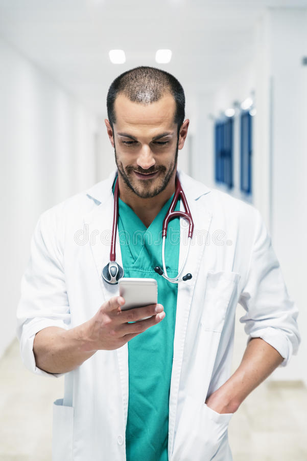 Beautiful doctor writting on cellphone at hospital. Indoors royalty free stock photography