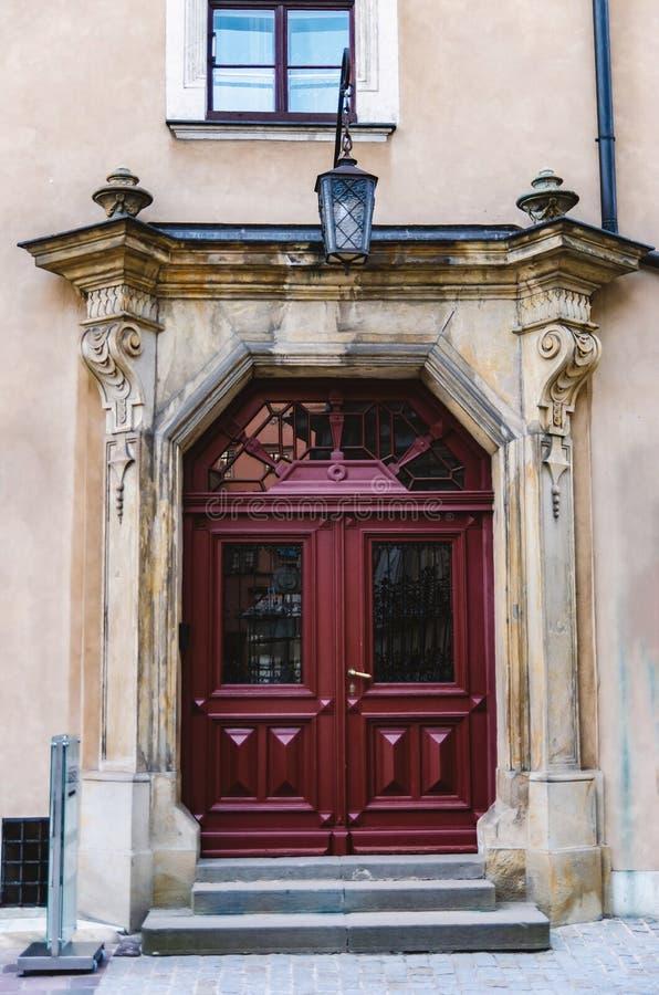 Beautiful double door burgundy wooden massive door in the old historic house royalty free stock photo