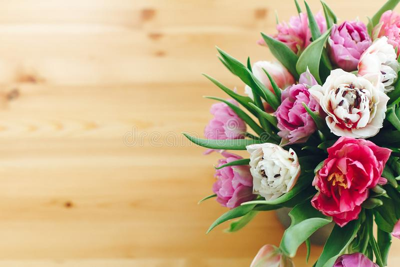 Beautiful double peony tulips in vase, top view with copy space. Colorful pink and purple tulips bouquet in vase. Happy mothers royalty free stock photography