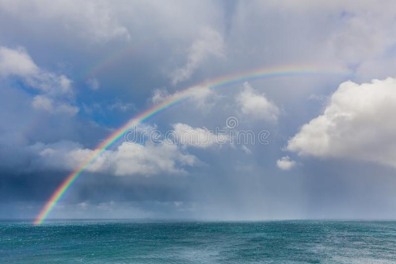 Beautiful double rainbow over ocean water with storm clouds in the sky closeup. stock photo