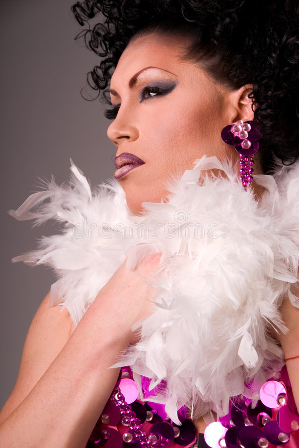 Beautiful Drag queen. Profile shot of a glamorous Drag queen wearing a pink beaded showgirl costume and feather boa stock photography