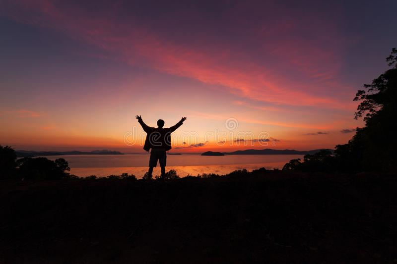 Beautiful dramatic sunrise with man standing raised-up arms enjoying freedom on the mountain. stock photography